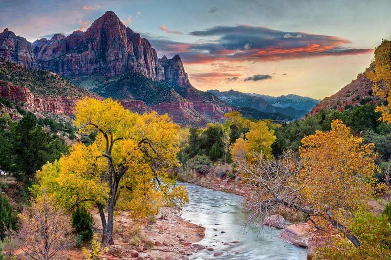 A river meanders through yellow and orange-leafed trees with a red rock cliff rising in the distance.