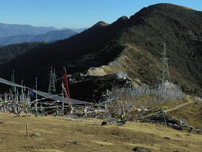 A profusion of prayer flags oddly compliment the power towers on Chele La